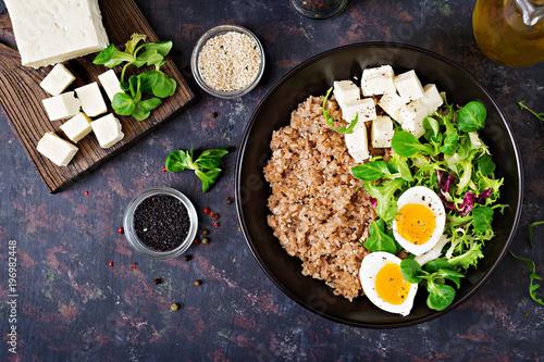 Plakat Zdrowe śniadanie z jajkiem, serem, sałatą i kaszą gryczaną na ciemnym tle. Odpowiednie odżywianie. Dietetyczne menu. Płaskie leżało. Widok z góry