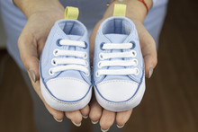 Woman Hand Holding Some Booties For Baby