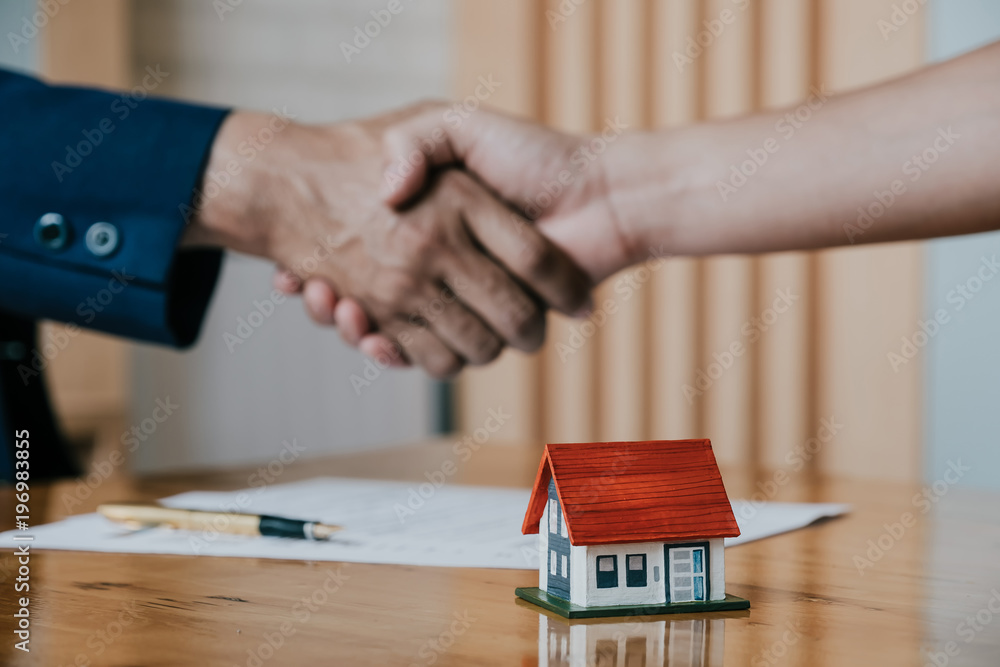 Fototapeta Estate agent shaking hands with his customer after contract signature, Contract document and house model on wooden desk