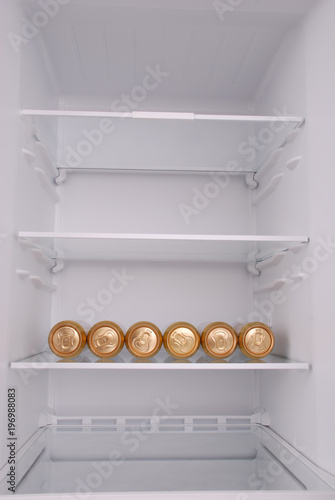 Six metal beer cans inside in empty clean refrigerator