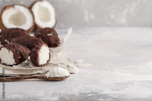 Photo Raw homemade vegan chocolate coconut candy bounty, white background, copy space