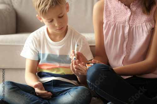 Fotografía  Woman and her diabetic son with lancet pen and glucometer taking blood sample at