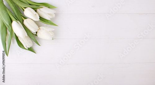 Bouquet of white tulips on a white wooden table, copy space. Easter.