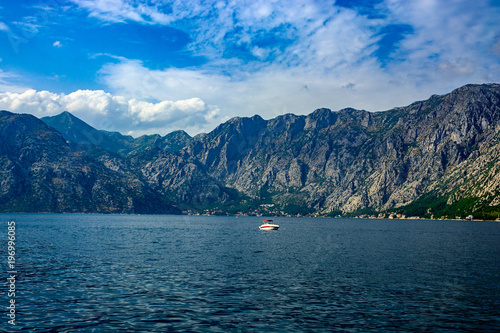 Plakat  Lonely modern boat in the sea against the background of the mountains