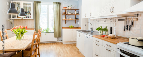 Obraz banner of a kitchen with kitchen table  and breakfast at the kitchen counter top white cupboards and wooden floor - fototapety do salonu