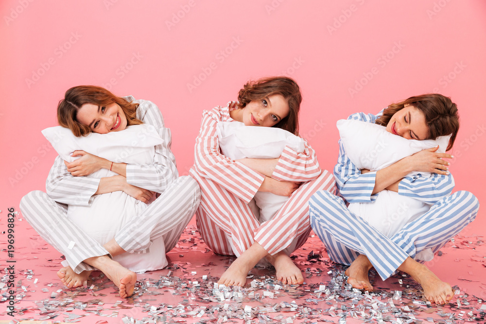 Fototapety, obrazy: Photo of sleepy women 20s wearing leisure clothings holding pillows and taking pleasure during slumber party, isolated over pink background
