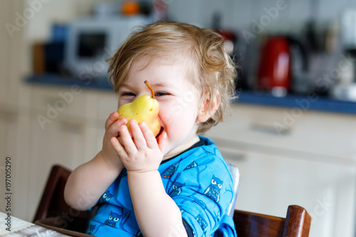 Fotografija Cute adorable toddler girl eating fresh pear