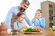 Portrait of smiling father teaching little girl cooking in kitchen while another daughter taking photo of family scene
