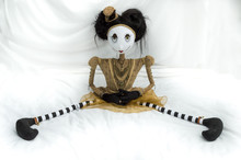 Creepy Steampunk Rag Doll Sitting With Legs Wide Apart. Facing Forward. High Angle View. Lifesize Doll On A Grungy White Background. Part Of A Series Of Different Poses.