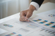 Hand of Businessman working on Data Charts,document at office desk. analyzing brainstorming, meeting concept..