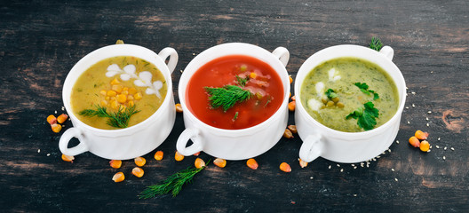 Fototapeta Set of hot, colored vegetable soups. Broccoli soup, corn, tomato soup. Healthy food. On a black wooden background. Copy space.