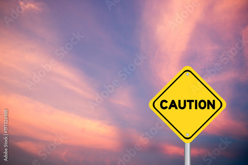 Fotografia Yellow transportation sign post with caution word on violet sky with cloud backg