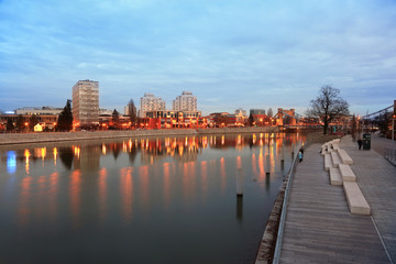 Fototapeta Budynki mieszkalne i most Grunwaldzki nad rzeką Odrą we Wrocławiu wieczorem.