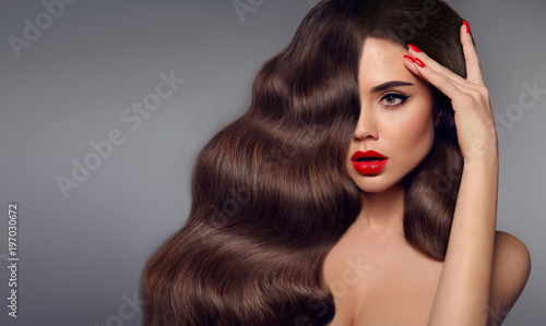 Obraz Beauty hair girl portrait. Red lips makeup, manicure nails and healthy wavy hairstyle. Sexy beautiful woman surprise looking to the side holds fingers near the head. Expressive facial expressions. - fototapety do salonu