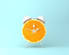 Creative Idea Layout Fresh Orange Slice Alarm Clock On Pastel Blue Background. Minimal Idea Business Concept. Fruit Idea Creative To Produce Work Within An Advertising Marketing Communications