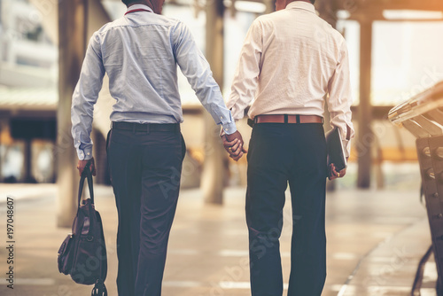 Pinturas sobre lienzo  Two Asian business men are walking hand in hand and taking care of each other