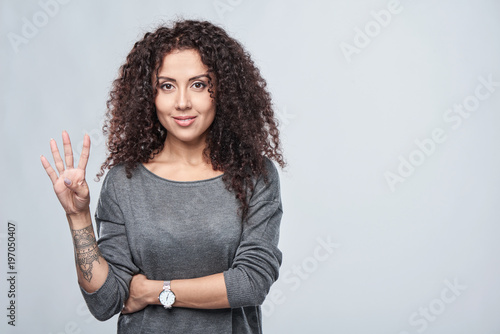 Hand counting - four fingers. Smiling woman showing four fingers Tableau sur Toile