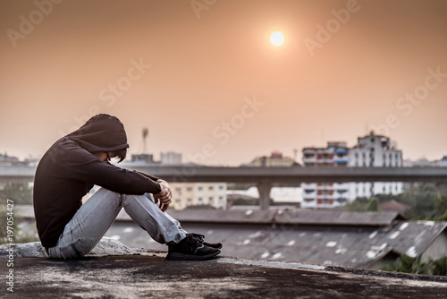 Obraz Young Asian man sitting on rooftop of abandoned building with depression stress out during sunset time in the city. Major depressive disorder concept - fototapety do salonu