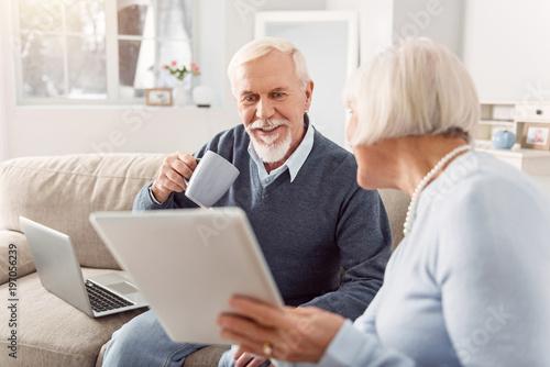 Plakat Spójrz. Przystojny starszy mężczyzna pije kawę i czyta artykuł na pastylce jego żona pokazuje on podczas gdy siedzący na leżance