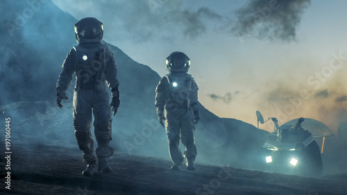 Two Astronauts in Space Suits Confidently Walking on Alien Planet, Exploration of the the Planet's Surface. In the Background Research Base/ Station and Rover. Space Travel, Colonization Concept.
