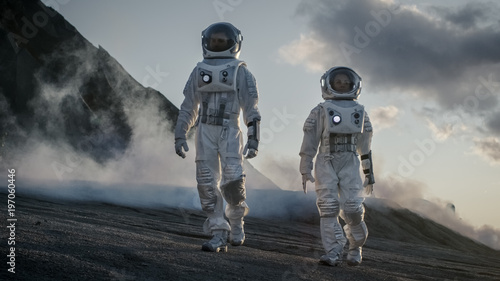 Photo  Two Astronauts in Space Suits Confidently Walking on Alien Planet, Exploration of the the Planet's Surface