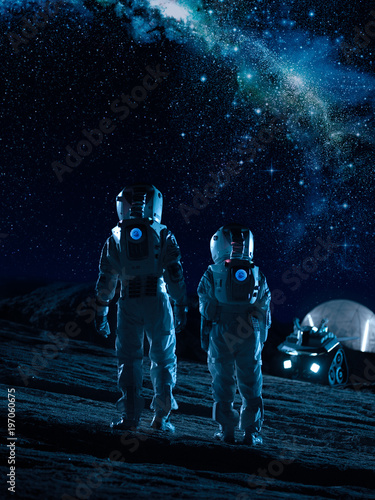 Two Astronauts in Space Suits Stand on the Alien Planets Looking at the Stars in Milky Way Galaxy. Space Travel and Extraterrestrial Colonization Concept. Wall mural