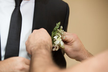Best Man Fixing Grooms Boutonniere. Groom Being Helped With The Buttonhole Flower On Lapel. Concept Wedding Day.