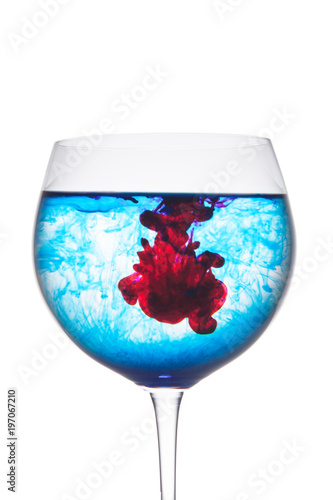 Food coloring diffuse in water inside wine glass area for slogan or advertising text message, isolated white background.