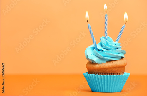 Photo  Birthday cupcake with candles on color background