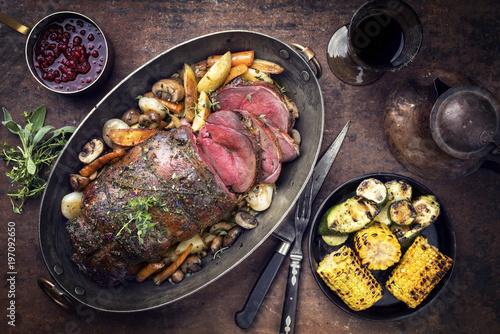 Barbecue dry aged Hirschkeule mit Pilzen und Gemüse als Draufsicht in einer Kasserolle