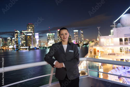 Woman steward on ship board at night in miami, usa. Sensual woman in suit jacket on city skyline. Water transport, transportation. Travelling for business. Wanderlust, adventure, discovery, journey