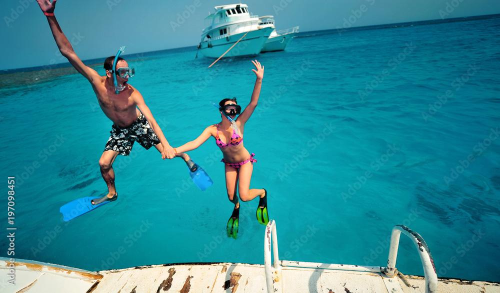 Fototapeta Happy young couple having snorkeling and beach fun on the yacht vacation honeymoon travel holidays. Caucasian woman and man playing playful enjoying love. Multiracial couple