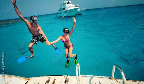Fotografia  Happy young couple having snorkeling and beach fun on the yacht vacation honeymoon travel holidays