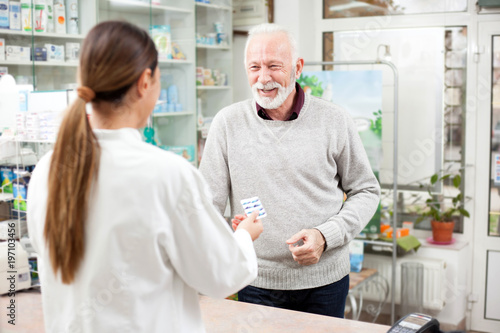 Spoed Foto op Canvas Apotheek Medicine, pharmaceutics, health care and people concept - Happy senior male customer paying for medications at a drugstore