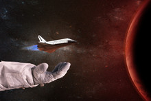 The Shuttle In The Hands Of The Astronaut Opposite The Red Planet. Elements Of This Image Furnished By NASA.