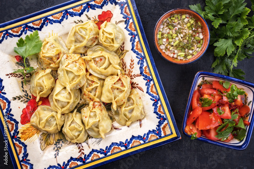 Traditional Kazakh manti steamed with mincemeat and tomato paprika salad as top view on a plate