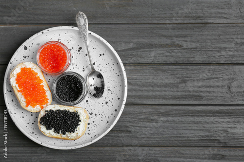 Jars and sandwiches with black and red caviar on plate