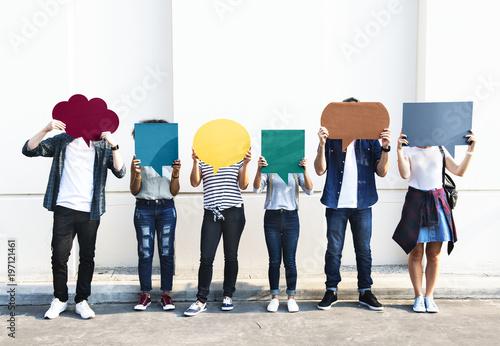 Obraz na plátně Young adult friends holding up copyspace placard thought bubbles