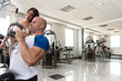 Man Train Back On Machine With Personal Trainer