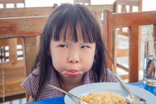 Fotografie, Obraz  Little asian girl refusing to eat fried rice for lunch