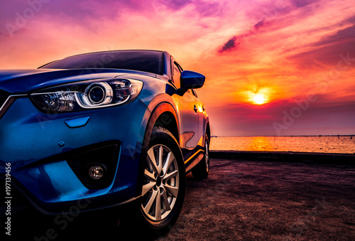 Leinwand Poster Blue compact SUV car with sport and modern design parked on concrete road by the sea at sunset