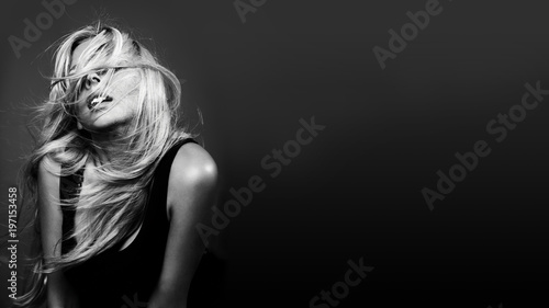 Beautiful young woman with curly blond hair. Fashion studio shot. Black and white image
