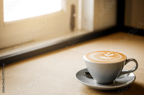 Spoed Fotobehang Cafe cup of coffee with heart pattern in a white cup on wooden background