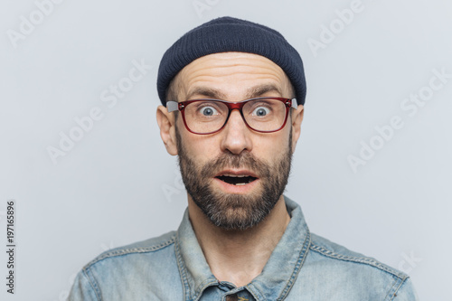 Fényképezés  Horizontal shot of amazed excited shocked man stares at camera with unexpected expression, keeps mouth opened, hears awful news, isolated over grey background