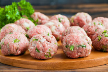 Raw Meatballs On Wooden Cutting Board And Fresh Parsley, Close-up