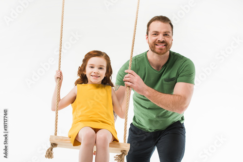 Fototapety, obrazy: Smiling father riding little daughter on swing isolated on white