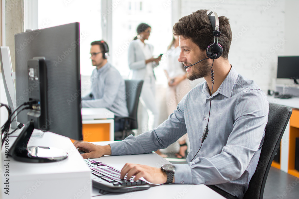 Fototapeta Smiling handsome customer support operator agent with hands-free device working in call center