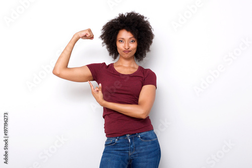 Fotografiet  fit young african woman pointing at arm muscles on white background