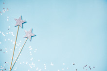 Two Silver Party Magic Wands And Scattered Sequins On A Blue Background. Copy Space.