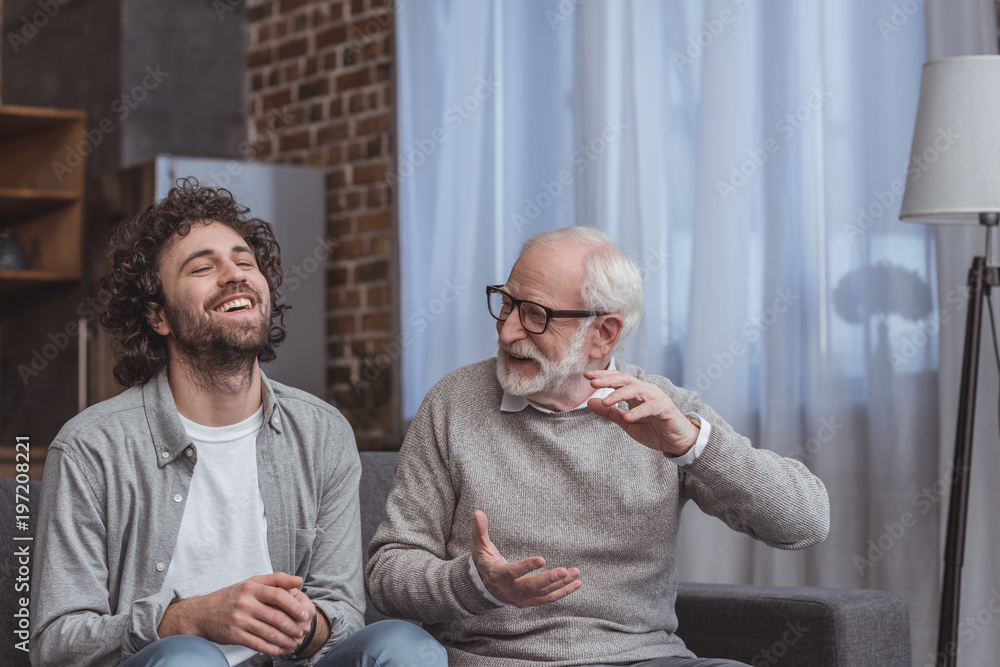 Fototapeta adult son and senior father talking and laughing at home